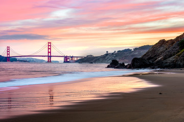 Beautiful Red dawn over the Golden Gate Bridge from a beach