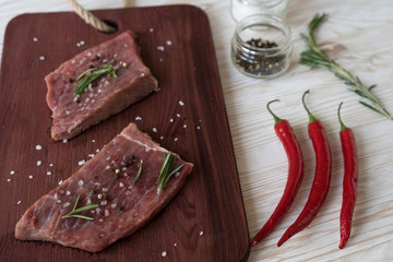 Fresh raw steaks with rosemary and pepper on wooden desk