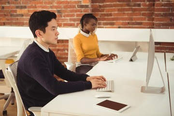 Male and female executives working at desk