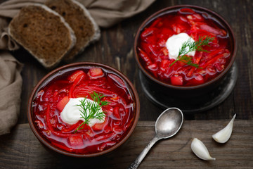 Vegan borscht in bowls on an old wooden background