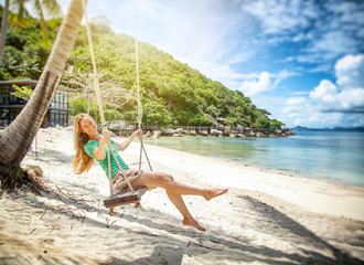 Happy young woman on vacation, on the seashore, swinging on a swing