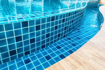Ceramic tile of swimming pool with water reflection.,