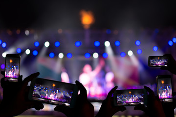 Silhouette of hands using camera phone to take pictures and videos at live concert.