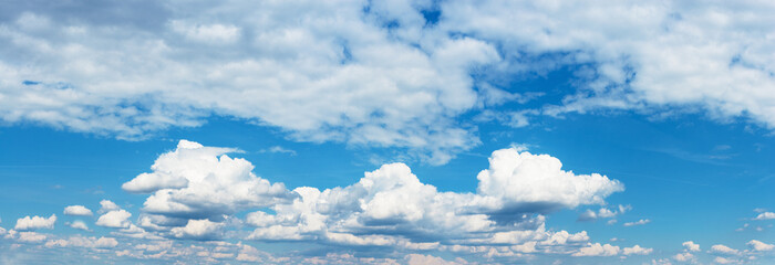 Blue sky with fluffy clouds. The feeling of space. Background. Horizontal frame view.