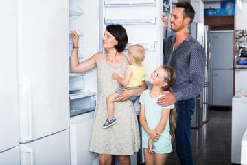 family choosing new freezer in store  .