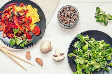 Healthy vegetarian diet concept. Rice and steamed vegetables, lamb's lettuce feldsalat on a black plates, chopsticks, napkin, garlic, mushrooms, raw multicolor rice in glass jar. White wooden table.
