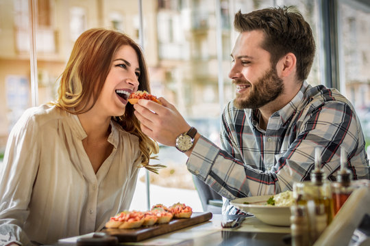 Cute Hispanic young couple having a good time together and sharing food in a coffee shop