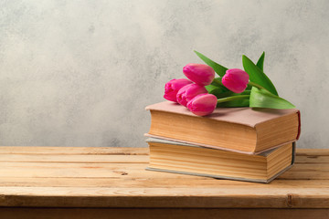 Tulip flowers and vintage books on wooden table with copy space