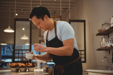 Male barista preparing dessert in coffee shop