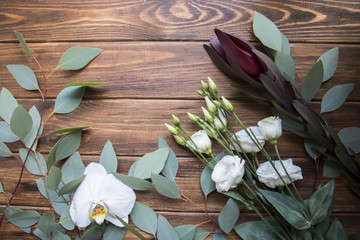 Branch eustoma flower, white orchid and eucalyptus leaves on rustic wooden background. View from above.