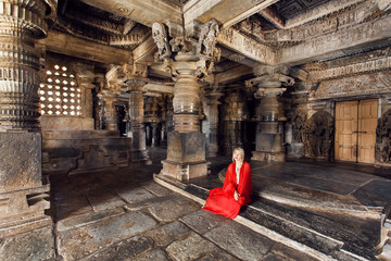 Beautiful woman in traditional indian dress sitting on stone floor of 12th century temple Hoysaleswara, India.