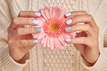 Fototapete - Pink gerbera with blue manicure.
