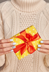 Fototapete - Beautiful yellow gift with a red bow against a knitted sweater background.