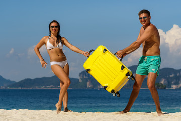 Young happy caucasian couple on a tropical beach with a suitcase
