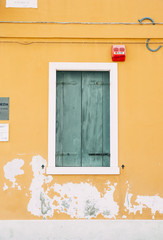 Beautiful yellow house wall with a wall crack and windows at Burano island in the north Italy