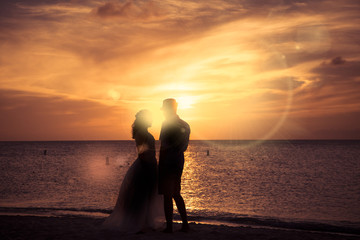 Silhouette of unrecognizable romantic couple at beach at sunset
