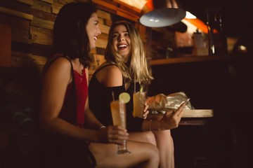 Beautiful women using mobile phone while having cocktail