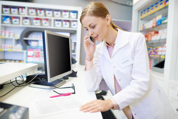 Pharmacist talking with customer by the phone