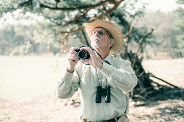 Senior man with hat photographing nature.