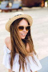 Cute girl in brown sunglasses and straw hat smiles charmingly. She wears white short dress with open shoulders. She has long dark slightly wavy hair.
