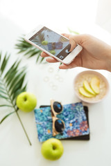 Woman hand taking summer pictures while eataing nutritious breakfast. Photography concept.