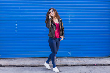 outdoors portrait of a beautiful Young woman talking on her smart phone over blue background. Casual clothing. lifestyle