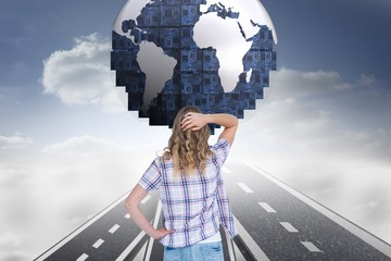 Digital composite image of confused woman looking at globe
