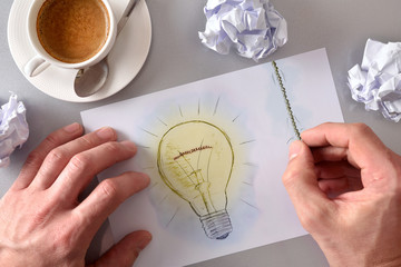Idea concept man lighting a light bulb drawn on sheet