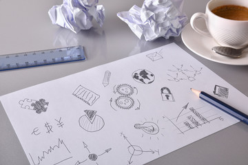 Sheet with drawings of relevant business concept on desk