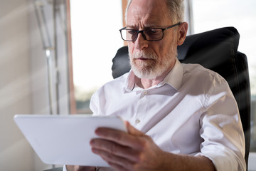 Senior businessman using a digital tablet, hard light