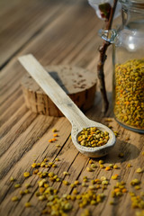 Grains of bee pollen in jar and wooden spoon on wooden table with flowers of spring trees. Apitherapy. Bee products.