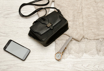 Black handbag, watch and mobile phone on a beige cardigan. Fashionable concept, top view