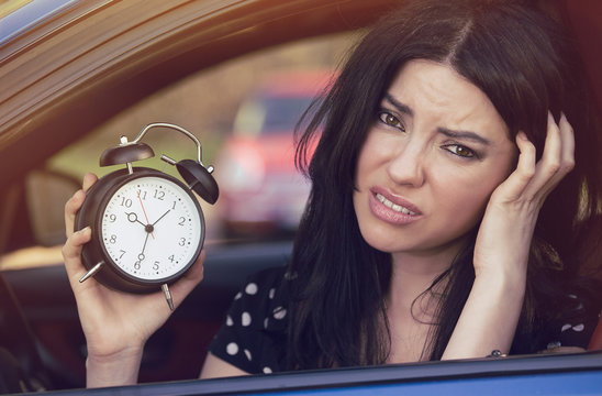Worried woman inside car showing alarm clock running late to work