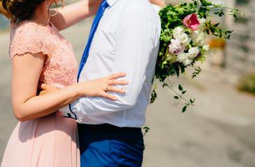 The bride is hugging the groom. Wedding in Montenegro.