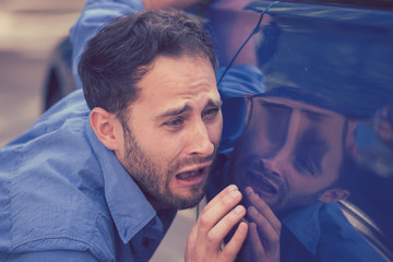 Upset man looking at scratches and dents on his car outdoors