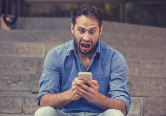 Shocked man looking at mobile phone seeing bad news or reading text message