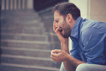 sorrowful crying man sitting on steps outdoors