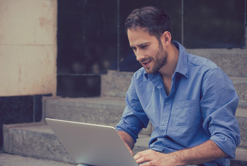 Happy man using his laptop computer outdoors smiling