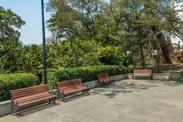 Wide view of group of unoccupied wooden seats or chairs arranged in a garden or park, Chennai, India, April 1st 2017