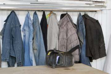 Dirty work clothes hanging on a hanger against a white wall.