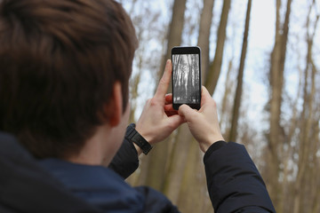 Man takes pictures of the park on a smartphone