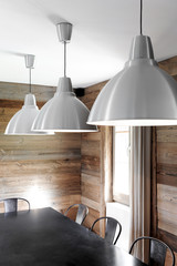 interior decoration of an old renovated wooden chalet with industrial-style dining room, black table, metal lamps and chairs and wooden wall