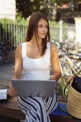 frau sitzt mit ihrem laptop draußen vor der universität