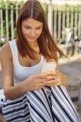 junge frau sitzt draußen und schaut auf ihr mobiltelefon