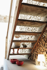 Wooden staircase, little girl and logs for the fireplace in an old renovated chalet