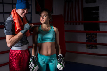 Sporty young woman in sportswear and in boxing gloves training with her couch