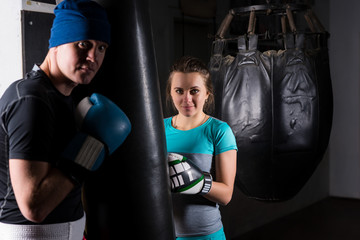 Young female spoty boxer in boxing gloves training with her trainer and boxing punching bag