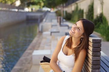 frau sitzt in der stadt am fluss und macht eine pause