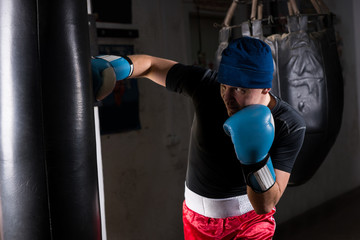 Young sporty man in a hat and boxing gloves training with boxing punching bag