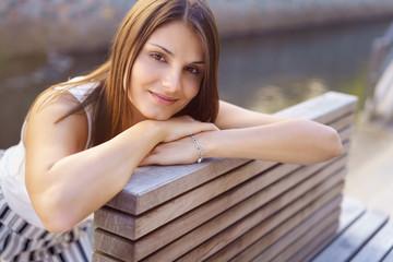 attraktive frau sitzt auf einer bank und stützt den kopf auf